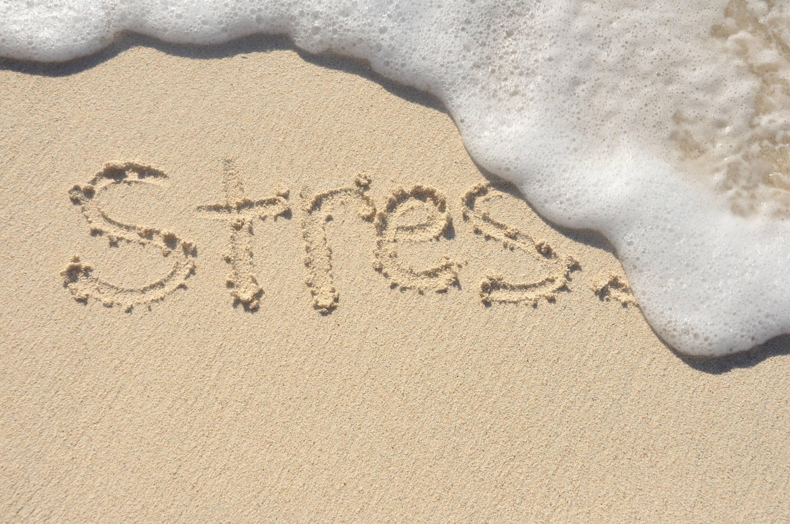 stress written in letters on a beach